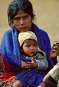 A mother sits smoking with her child on her  lap, Nepal