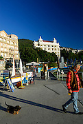 Man walking dog on leash, past advertising sandwich-boards, with Grand Hotel Palace in background. Opatija, Croatia