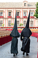 Two penitents walk in the fenced area used as a grandstand in front of the Cathedral of Seville. Tickets for the processions get sold-out very quickly. Andalusia, Spain.