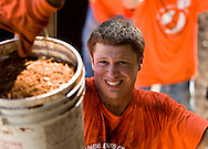ING DIRECT employee Tyler Fore hoists a bucket during the Orange Days of Giving. Client: ING Direct. (Photo/John Froschauer)