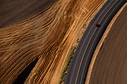 Aerial image of a red car driving on a country road through the wheatfields in the Palouse, eastern Washington, Pacific Northwest by Randy Wells