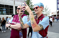 An Aston Villa fan takes photos on her phone outside of the stadium before the match begins