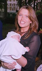 Actress TINA HOBLEY and her daughter ISABELLA, at a cricket match in London on 14th June 1999.MTE 100