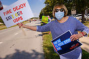 22 AUGUST 2020 - DES MOINES, IOWA: SUE AMOSSON, from West Des Moines, stands on the median of 2nd Ave in front of the main US Post Office in Des Moines during a rally in support of the USPS. About 35 people picketed the main US Post Office in Des Moines Saturday protesting changes made to the Postal Service by the Trump Administration. Nationally, there has been concern that changes to the Postal Service will hurt citizens' ability to vote by mail in the 2020 presidential election.        PHOTO BY JACK KURTZ