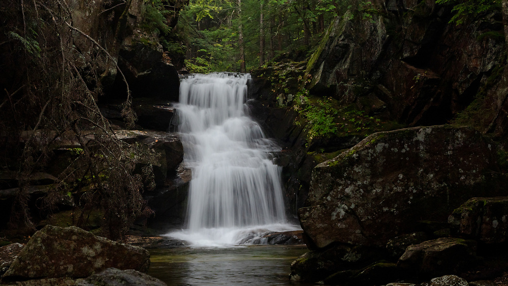 Mountain water rushing through the rocky canyon at Cold Brook Falls in the woods of the White Mountains.