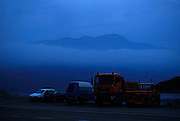 Heavy pre-dawn mist covers sea, with cars and trucks in foreground, Island of Korcula, Croatia