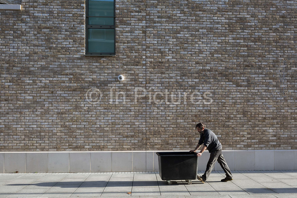 A man pushes a bin on wheels beneath new housing at Elephant Park, on 30th January 2018, in the south London borough of Southwark, England.