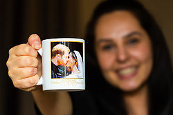 Deputy Hotel Manager Nicky Gashtasbi poses with a mug commemorating the wedding of Harry and Meghan left in one of the hotel's rooms. London, July 24 2019.