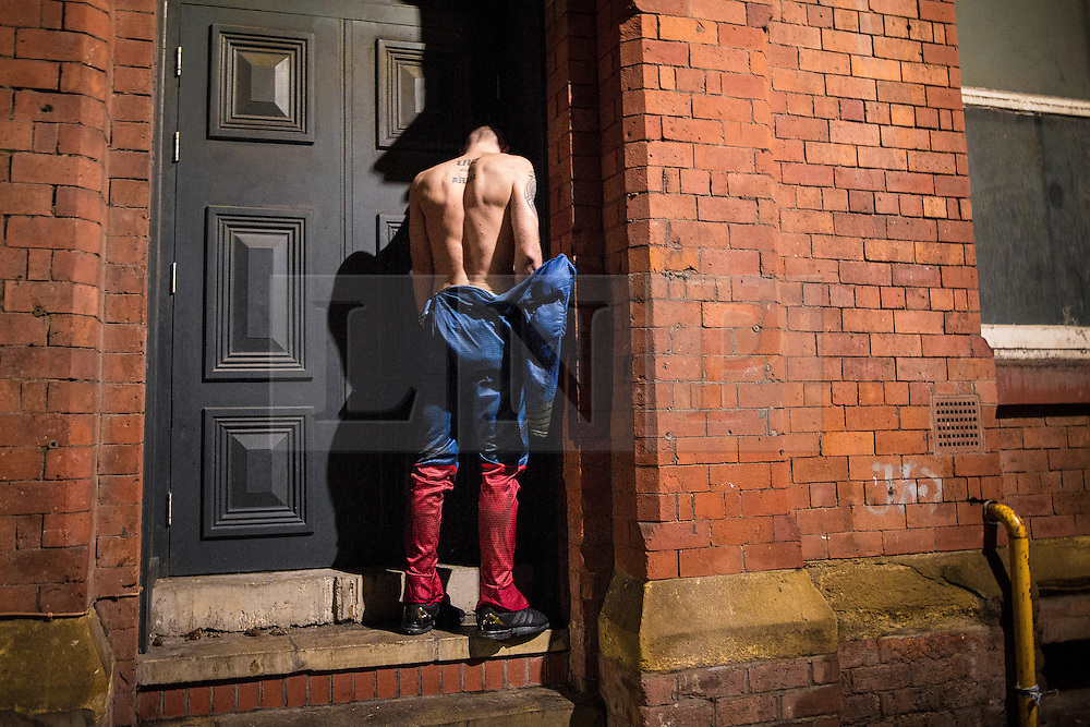 © Licensed to London News Pictures . 27/12/2015 . Wigan , UK . A man dressed as Superman urinates in a doorway . Revellers in Wigan enjoy Boxing Day drinks and clubbing in Wigan Wallgate . In recent years a tradition has been established in which put on fancy dress for a Boxing Day night out . Photo credit : Joel Goodman/LNP