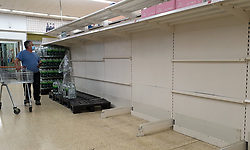 © Licensed to London News Pictures. 03/08/2021. London, UK. A shopper wearing a face covering walks past empty shelves of bottled drinking water in Sainsbury's, north London. It has been reported that Britain could face a shortage food and drink supplies and these are likely to continue for several months, due to a lack of lorry drivers. Photo credit: Dinendra Haria/LNP