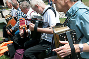 East End, London July 5th 2014. Rally and march against proposed cuts to National Health Service doctors' surgeries, specifically MPIG (Minimum Practice Income Guarantee payments) brought in to ensure practices in deprived areas had enough money to deliver high quality General Practice services.Members of the Yardarm folk orchestra play melodiums in Altab Ali Park, Whitechapel, before the march.