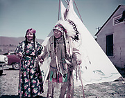 """9305-B7076. The last public appearance of Chief Tommy Thompson, photographed here with his wife Flora, as they were arriving in Celilo for the Feast of the First Salmon on Saturday, May 11, 1957. Chief Thompson, age 102, came to """"say a few words of farewell"""" to the salmon and the falls at the annual festival being held just two months after Celilo had been permanently submerged by the backwaters of The Dalles Dam. After the ceremonies and an overnight stay in Celilo village, he returned to his room at the Hanby nursing home in Hood River. According to newspaper accounts, on the night of his return he had nightmares, which caused him to climb over the guardrails of his bed, when he fell and fractured his right hip. He was taken to the Hood River Memorial hospital where surgeons placed a steel pin in his hip. The next year's Salmon Feast was held in Tommy Thompson's honor, but the elderly Chief never again personally attended. He lived two more years and passed away on April 12, 1959."""