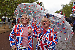 Licensed to London News Pictures. 05/06/2012. LONDON, UK. Spectators take shelter from the rain on the Mall during a fly past of WWII aircraft and the Red Arrows. Great Britain is celebrating the 60th  anniversary of the countries Monarch HRH Queen Elizabeth II accession to the throne this weekend Photo credit : Cliff Hide/ LNP