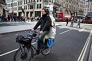 Man cycling with his cello along Regent Street in central London, UK.