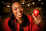 A teacher smiles and holds an apple while standing in her school's gymnasium.