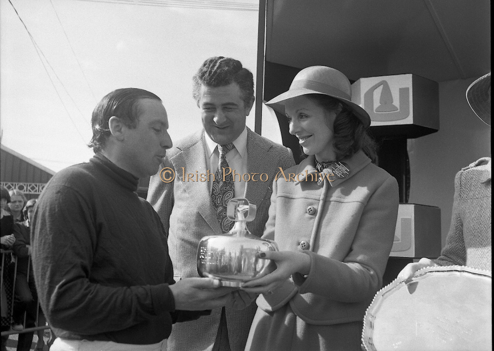 """Irish Distillers Grand National at Fairyhouse.  (M66)..1979..16.04.1979..04.16.1979..16th April 1979..The Irish Distillers Grand National was run today at Fairyhouse Racecourse, Co Meath.The race over 3.5miles is valued at £20,000. the winning trainer will also receive the Tom Dreaper,Perpetual Trophy which will be presented by Mrs Betty Dreaper..Image shows owner and rider ,Anthony Robinson ,of the winning horse """"Tied Cottage"""" accepting the winner's trophy from Mrs MichaelO'Kennedy,wife of the Minister of Foreign Affairs,included in the picture is Mr Richard Burrows,Managing Director,Irish Distillers Ltd."""