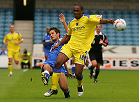 Photo: Frances Leader.<br />Millwall v Cardiff City. Coca Cola Championship.<br />24/09/2005.<br /><br />Cardiff's Cameron Jerome is tackled by Millwall's Mark Phillipd.