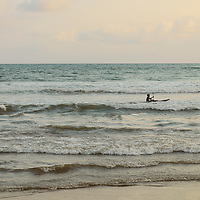 Boy rowing a small canoe through the waves.