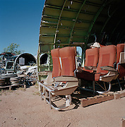 Economy class seats in mid-day heat of arid Sonoran Desert at Mojave airport facility, awaiting recycling for scrap value.