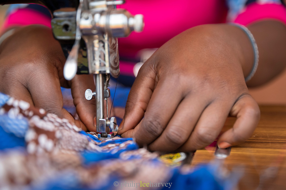 Close-up of woman working with sewing machine in Design and Tailoring Centre, Musoto, Uganda