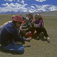 Khyrgiz nomad children laugh with their family in the Pamir Mountains of Xinjiang province in far-western China. 7,546-meter [Mount] Mustagh Atatowers in the background.