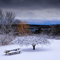 Fresh snow covers a picnic table and the beauty of the Miane countryside.  View down to the Damariscotta River.