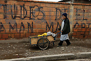 Bolivia. 2010. El Alto. Woman pushes cart with bananas.
