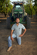 Bryan Harper, Hazelnut farmer, poses with one of his tractors.