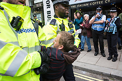 London, UK. 8 October, 2019. Metropolitan Police officers arrest a climate activist from Extinction Rebellion who had blocked Marsham Street in front of the Home Office on the second day of International Rebellion protests to demand a government declaration of a climate and ecological emergency, a commitment to halting biodiversity loss and net zero carbon emissions by 2025 and for the government to create and be led by the decisions of a Citizens' Assembly on climate and ecological justice.