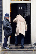 © Licensed to London News Pictures. 25/04/2012. Westminster, UK . A man walks into Downing Street with his coat over his head to avoid the rain. The Prime Minister David Cameron leaves Downing Street today 25 April 2012 for Prime Ministers Questions at the Houses of Parliament. Photo credit : Stephen Simpson/LNP