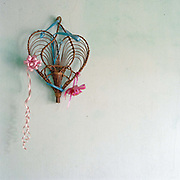 A bamboo heart shaped decoration hanging on a green painted wall in Tran Phu village, Ha Tay province, Vietnam