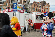 A couple eats a snack while mickey mouse is making balloons in forms of animals on this market in the town of Anderlecht near Brusels. Medieval houses in the background, and a hot-dog stand called Chez Betty Hamburger.