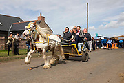 A laughing group of men driving a white horse and yellow wagon at the foot of the flash, a strip of dirt road where people show off their horses at Appleby Horse Fair, the biggest gathering of Gypsies and travellers in Europe, on 14th August, 2021 in Appleby, United Kingdom. Appleby Horse Fair attracts thousands from Gypsy, Romany, and traveller communities annually, making it the biggest gathering of its kind in Europe. Generally held for a week every June, the fair was postponed in 2020 and pushed forward to August in 2021 due to Coronavirus.