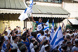 © Licensed to London News Pictures . 05/06/2016 . Jerusalem , Israel . Thousands of Jews with flags process through Damascus Gate , through the Old City's Muslim district , on the way to the Western Wall , separated from residents of the Old City's Muslim district by Israeli soldiers . Israeli Jews celebrate Jerusalem Day . Photo credit : Joel Goodman/LNP