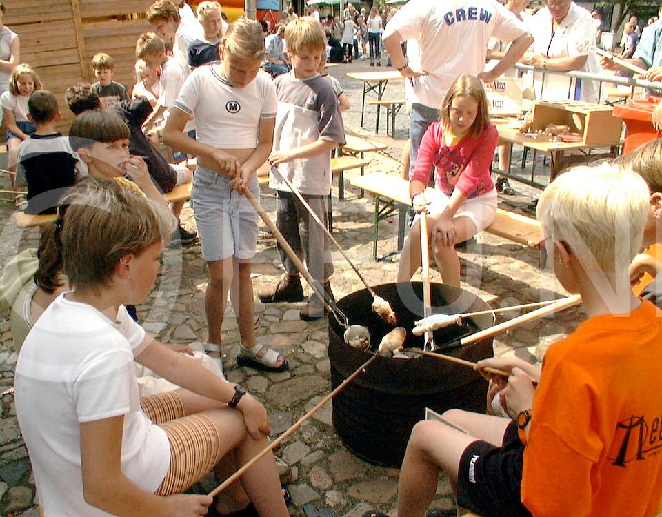 Fotografie Frank Uijlenbroek©2000/michiel van de velde.000611 raalte ned.fu000611_06.ribs en bluesfestival in het centrum met optredens van verschillende bands het was er zeer druk.hier zijn een stel kinderen brood aan het bakken op de ouderwetse manier
