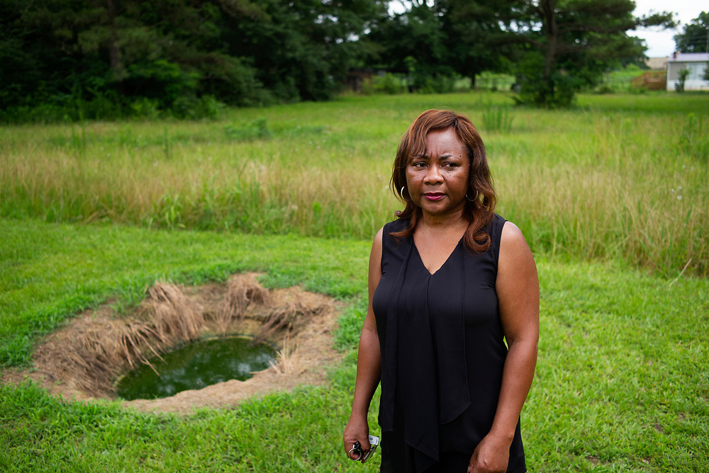 WHITE HALL, AL – MAY 28, 2015: Catherine Coleman Flowers stands over a pool of raw sewage outside a home in White Hall, Alabama. For over a decade Flowers has worked as an advocate in the Black Belt, where improper sewage treatment has put the population at risk of diseases long believed to be extinct in the United States.