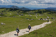Walkers decend towards the collection of Slovenian herders mountain huts in Velika Planina, on 26th June 2018, in Velika Planina, near Kamnik, Slovenia. Velika Planina is a mountain plateau in the Kamnik–Savinja Alps - a 5.8 square kilometres area 1,500 metres 4,900 feet above sea level. Otherwise known as The Big Pasture Plateau, Velika Planina is a winter skiing destination and hiking route in summer. The herders huts became popular in the early 1930s as holiday cabins known as bajtarstvo but these were were destroyed by the Germans during WW2 and rebuilt right afterwards by Vlasto Kopac in the summer of 1945.