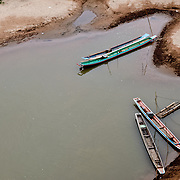 Wooden canoes moored on riverbank of Nam Ou (River Ou) in Nong Khiaw in northern Laos. The sandy bottom of the river means that the current creates small, sandy islands and protected inlets on the river.