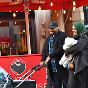 A couple of Muslim smiling walking pass at Leicester Square, London, UK 23 September 2018.
