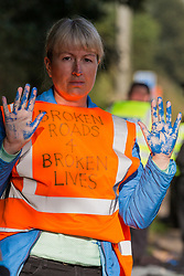 Ockham, UK. 21st September, 2021. An Insulate Britain climate activist holds up her hands covered in blue paint before being arrested by Surrey Police after blocking the clockwise carriageway of the M25 between Junctions 9 and 10 as part of a campaign intended to push the UK government to make significant legislative change to start lowering emissions. Both carriageways were briefly blocked before being cleared by Surrey Police. The activists are demanding that the government immediately promises both to fully fund and ensure the insulation of all social housing in Britain by 2025 and to produce within four months a legally binding national plan to fully fund and ensure the full low-energy and low-carbon whole-house retrofit, with no externalised costs, of all homes in Britain by 2030.