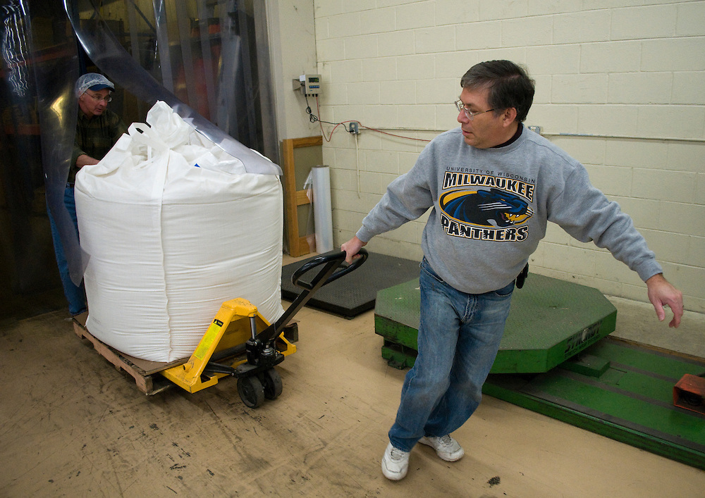 Mark Gottlieb (right) helps unload a 2 ton bag of rice with Ed Quetin.