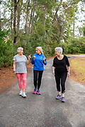 A group of senior woman exercising together on a path outside