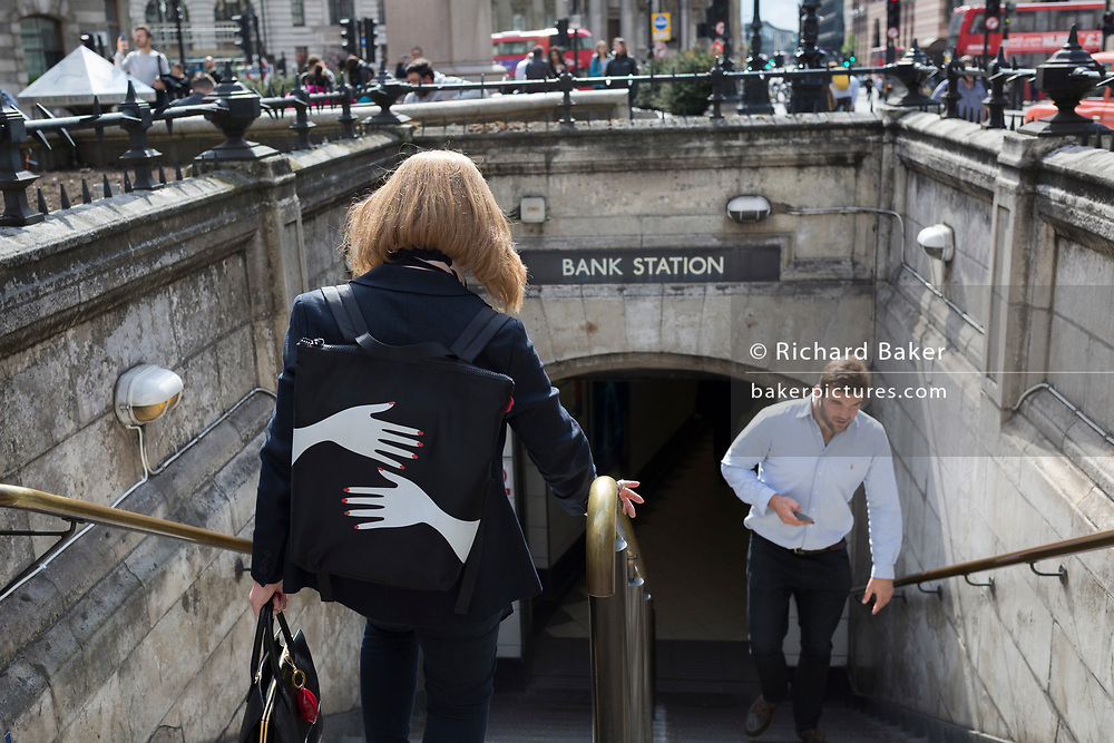 A lady wearing a small rucksack which features two manicured feminine hands holds on to the central rail and descends steps into Bank underground station, in the City of London, the capital's financial district, on 10th May 2019, in London, England.
