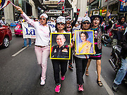 """14 JULY 2013 - BANGKOK, THAILAND:  Royalist supporters of the Thai monarchy carrying photos of Bhumibol Adulyadej, the King of Thailand, and his wife, Queen Sirikit, march in Bangkok Sunday. About 150 members of the so called """"White Mask"""" movement marched through the central shopping district of Bangkok Sunday to call for the resignation of Yingluck Shinawatra, the Prime Minister of Thailand. The White Mask protesters are strong supporters of the Thai monarchy. They claim that Yingluck is acting as a puppet for her brother, former Prime Minister Thaksin Shinawatra, who was deposed by a military coup in 2006 and now lives in exile in Dubai.       PHOTO BY JACK KURTZ"""