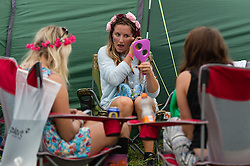 © Licensed to London News Pictures. 05/09/2014. Isle of Wight, UK. Festival goers apply their festival makeup at Bestival 2014 Day 2 Friday.  This weekend's headliners include Chic featuring Nile Rodgers, Foals and Outcast Photo credit : Richard Isaac/LNP
