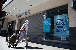 "© Licensed to London News Pictures. 13/06/2020. London, UK. A shopper wearing a face covering walks past ""TAKE CARE STAY SAFE' sign on display at Primark in Wood Green, north London as the store prepares to re-open on Monday. The government has announced that all non-essential retailers can re-open on Monday 15 June as the coronavirus lockdown restrictions are eased. Photo credit: Dinendra Haria/LNP"