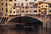 Rowing in a scull on the Arno River under the Ponte Vecchio. Florence, Italy.