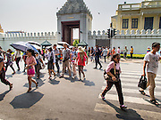15 OCTOBER 2014 - BANGKOK, THAILAND: Tourists cross the road in front of the Grand Palace in Bangkok. The number of tourists arriving in Thailand in July fell 10.9 per cent from a year earlier, according to data from the Department of Tourism. The drop in arrivals is being blamed on continued uncertainty about Thailand's political situation. The tourist sector accounts for about 10 per cent of the Thai economy and suffered its biggest drop in visitors in June - the first full month after the army took power on May 22. Arrivals for the year to date are down 10.7% over the same period last year.   PHOTO BY JACK KURTZ