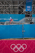 With the Olympic rings logo below, a Slovakian sports supporter carries his national flag up towards his seat before the start of the canoe slalom heats at the Lee Valley White Water Centre, north east London, on day 3 of the London 2012 Olympic Games.