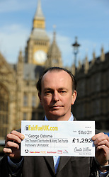 ©London News pictures. 10/03/11.Quentin Willson holds up a fair fuel 'cheque' representing the amount of duty an average motorist pays of fuel duty per year. Quentin Willson leads a Fuel Tax protest on College Green outside Parliament, holding a giant cheque to represent the £26 billion Britons pay in fuel duty each year, the campaign was organised by www.fairfueluk.com. Picture Credit should read Stephen Simpson/LNP